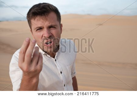 angry man shouting accusing someone standing in desert alone