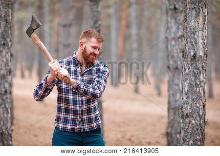 A woodcutter with ginger hair and a beard in a blue checkered shirt swings an ax at something. Outdoors.