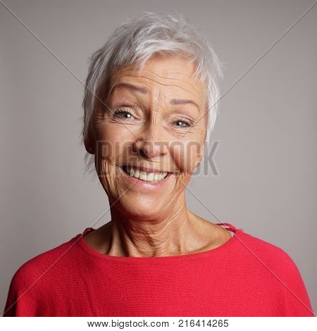 happy older woman in her 60s with trendy short white hair laughing