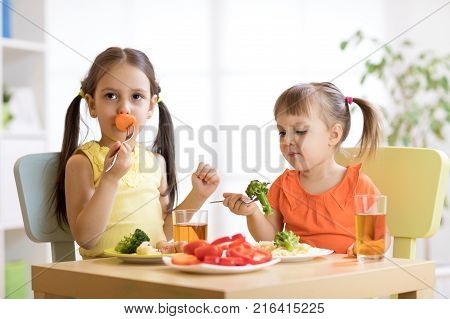 Little discontented children does not want to eat a pasta with vegetables