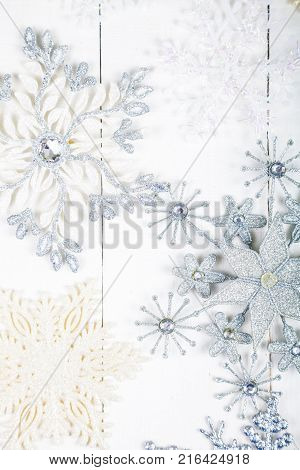 Silvery snowflakes on a white wooden background. Christmas decor.