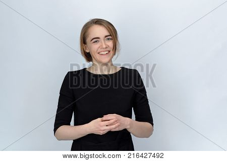 Studio portrait of a young woman with a wide smile and narrowed eyes isolated on a white background and concatenated in front of her hands