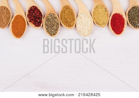 Multicolored asian spices in quaint spoons on white wooden background. Top view.