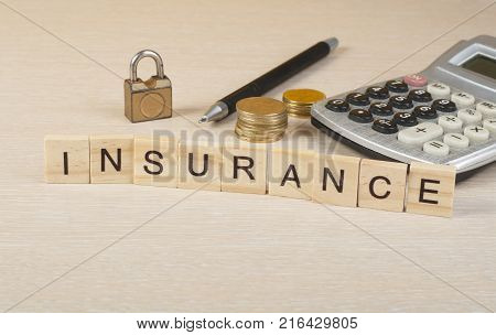 Insurance and saving concept. Wooden blocks with the text INSURANCE. Calculator, coins and padlock on the table