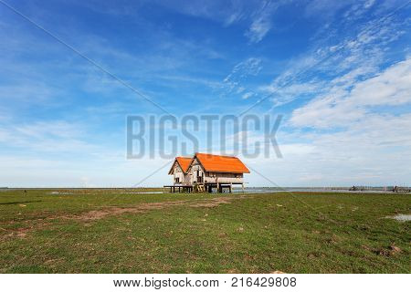 old house at Thale Noi with blue sky Chaloem Phrakiat Bridge Phatthalung province in Thailand