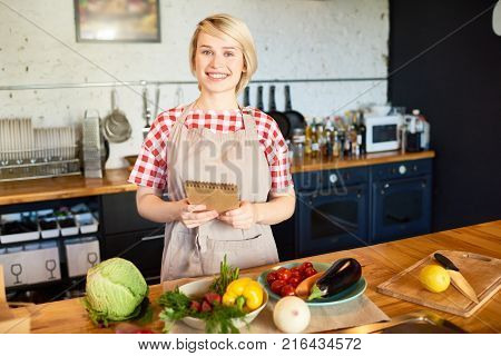 Cheerful blond-haired housewife wearing checked shirt and apron looking at camera with toothy smile while standing at kitchen table and holding notepad with recipe in hands, waist-up portrait
