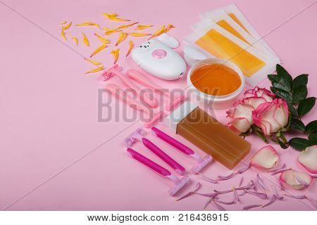 A female epilator and six disposable pink razors, wax strips, wax, wax cachet with roses, lie on a pink background, free space for text.