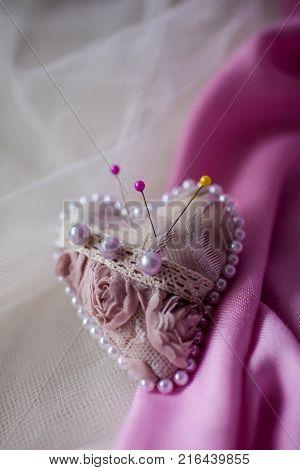 Pink pincushion heart on a light background. Handmade.