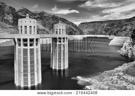 Hoover Dam Towers on the blue Lake Mead. Hoover Dam is a concrete arch-gravity dam in the Black Canyon of the Colorado River on the border between the U.S. states of Nevada and Arizona.
