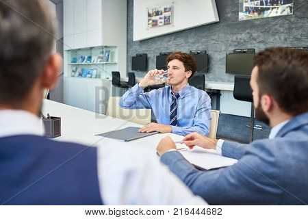 Working meeting at full speed: group of white collar workers gathered together at boardroom and sharing ideas concerning start-up project, handsome man drinking glass of water