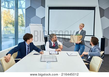 Group of white collar workers distracted from project discussion and looking at pretty middle-aged colleague with cardboard box in hands, interior of spacious boardroom on background