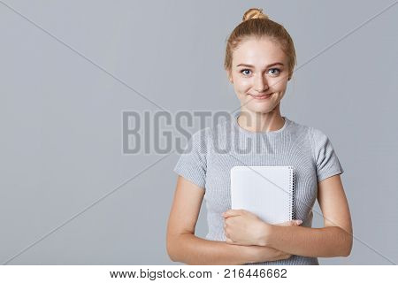 Young College Student Holds Spiral Diary Or Notebook, Reads Information Or Notes, Prepares For Exami