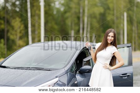 Happy woman driver showing car keys and leaning on car door