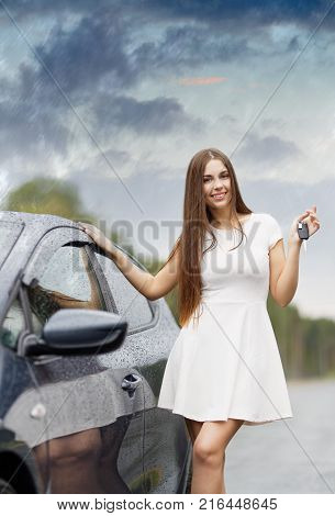 Happy woman driver showing car keys and leaning in the rain