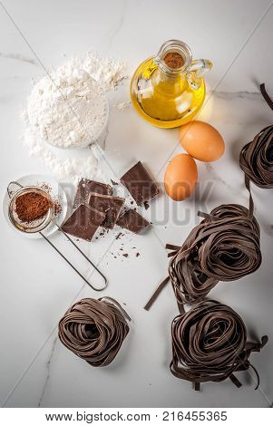 Raw unprepared chocolate pasta noodles with ingredients for cooking - chocolate cocoa flour eggs oil. On a white kitchen marble table. Copy space top view