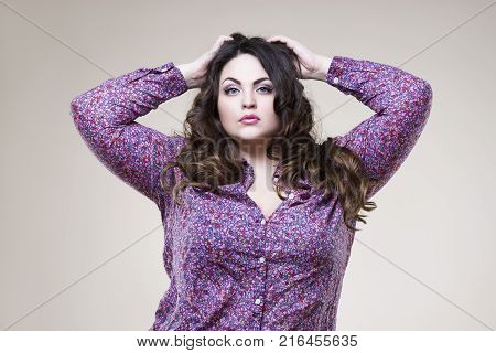 Plus size fashion model in casual clothes sexy fat woman on beige studio background