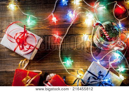Christmas New Year's concept. Mason Jar with decorations fir cones artificial snow candy cane and fir branch. On a wooden table background with a lit garland turned on. Copy space top view frame