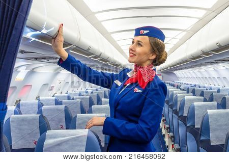 Charming Stewardess Dressed In Uniform In The Passenger Cabin Of The Aircraft. Russia, Saint-petersb