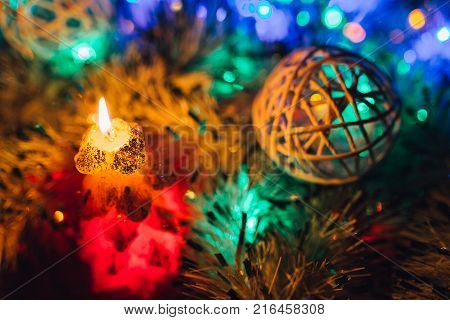 Burning candle and Christmas decoration over snow and wooden background elegant low-key shot with festive mood