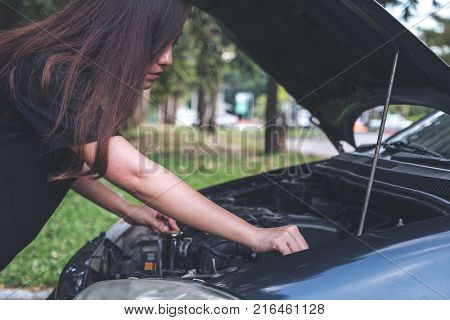 Woman try to fixing broken old car with outdoor background