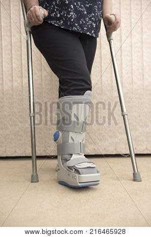 Unrecognisable woman wearing a support boot with crutches