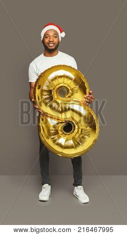 Happy black man with number 8 balloon portrait. African-american boy in santa hat at studio background. One of shots to compose 2018 for new year and christmas greeting card