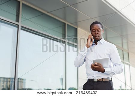 Happy black businessman with smartphone and tablet outdoors. Young african-american salesman working with mobile and digital device, standing in urban area cityscape