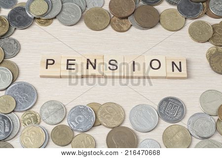 Word PENSION on wooden cube with frame of coins at wood background. Pension budget concept.