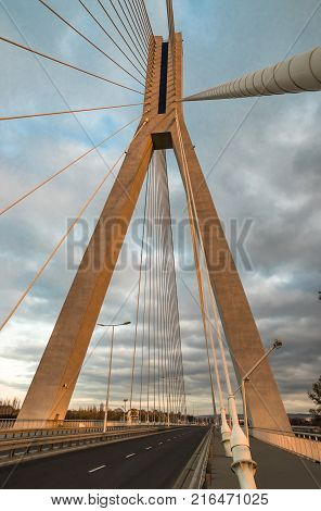 Highway going through a cable-stayed bridge with big steel cables, close-up in the evening during a sunset against a background of sky and clouds