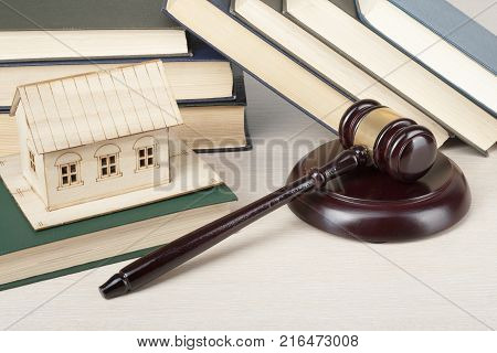 Law concept Miniature house, book with wooden judges gavel on table. Property concept .