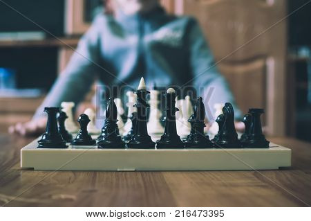 little boy playing chess. home pastime. Board with chess on a wooden table. Children playing chess.