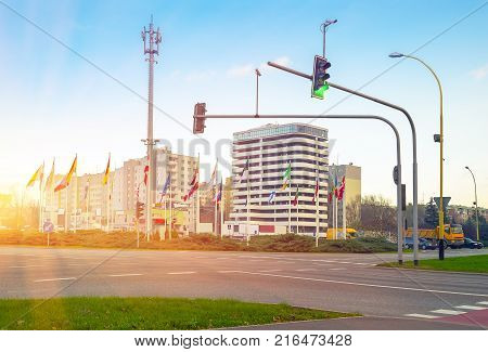 Crossroad and flags countries near roadway against backdrop large modern business office building and multi-apartment buildings