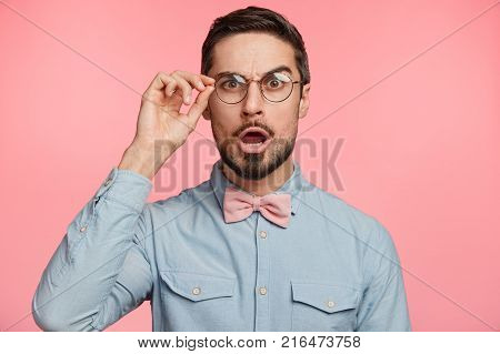 Portrait of satisfied amazed man with beard opens mouth says wow being astonished to see something keeps hand on cheeks isolated over pink background. People reaction and emotions concept poster