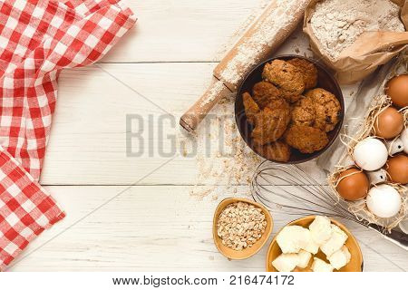 Cooking ingredients for sweet oatmeal cookies background. Eggs, butter, flour, spices and kitchen utensils on white wood. Recipe or baking classes mockup, pastry making concept, top view, copy space