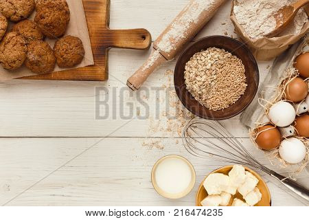 Cooking ingredients for homemade oatmeal cookies. Oat flakes, eggs, butter, milk and kitchen utensils at white rustic background with copy space, top view. Handmade pasty concept and recipe mockup