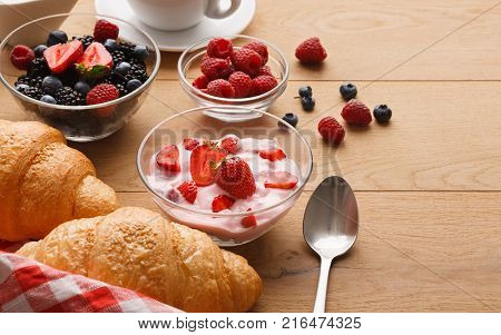 Rich continental breakfast. French crusty croissants, greek yogurt, cup of hot black coffee and lots of sweet berries for tasty morning meals. Delicious start of the day