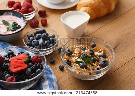 Rich continental breakfast. French crusty croissants, muesli, greek yogurt, milk jar for coffee and lots of sweet berries for tasty morning meals. Delicious start of the day
