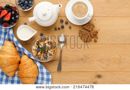 Rich continental breakfast background. French crusty croissants, muesli, lots of sweet berries and hot coffee for tasty morning meals. Delicious start of the day. Top view, copy space on natural wood
