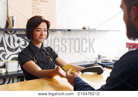 Beautiful smiling barista taking credit card from customer to pay for beverage at coffee shop counter. Small business, occupation people, payment and service concept, copy space