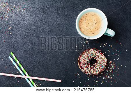 Cozy breakfast with colorful donut and fresh coffee on black table top view. Flat lay. Copy space.