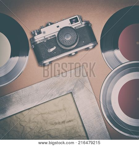 Retro things set. Vintage film camera, old vinyl records, shabby wooden frame with aged paper. Nostalgic mood concept