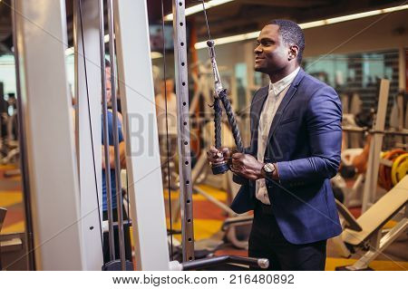 Exercise for triceps in the gym. African bussinesman in classic suit performs an exercise on the triceps in the simulator. fitness in gym.