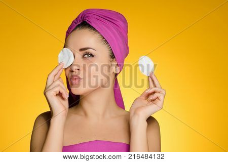 a funny young girl cares for her face, cleans the skin and face with white cotton pads