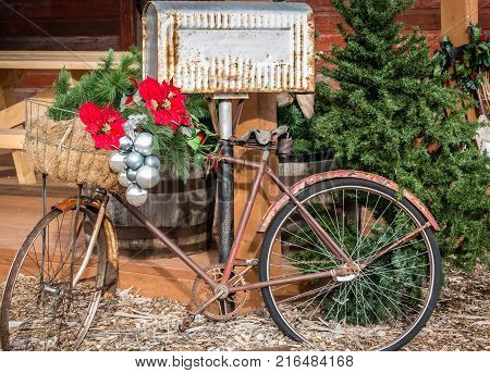 Christmas image of a very old rusty bike decorated with Christmas decoration and silver balls leaning against an old Tin mailbox.
