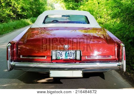 NEVINOMYSSC, RUSSIA - MAY 13, 2016: Automobiles. Offsite photography of old American cars. Cadillac Eldorado Convertible 1976s. View of Rear view of machine on a country road in a green forest