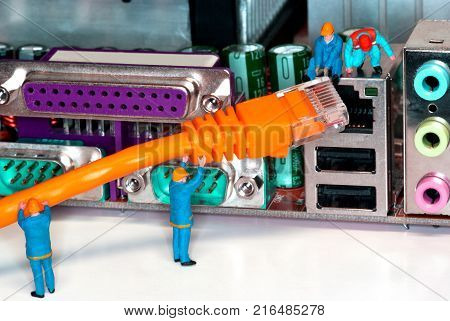 Computer Network Internet Cable - Miniature construction worker figurines posed as if working on a network connection.
