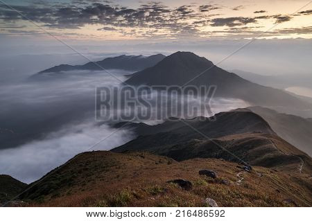 Clouds rolling over a mountain on Lantau Island, viewed from the Lantau Peak (the 2nd highest peak in Hong Kong, China) at dawn.
