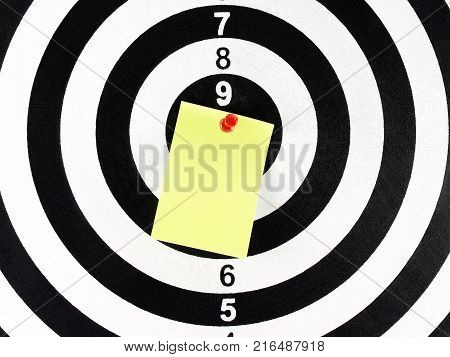 close-up blank yellow paper note with red pushpin on target center of dartboard, message for goal and achievement
