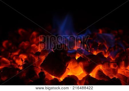 Close-up of glowing hot red embers (coal) and blue flame in fireplace.