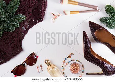 Fashion Christmas flat lay scene. Dress, hight heel shoes and evergreen tree twig, dressing up for Christmas party fashion accessoires frame